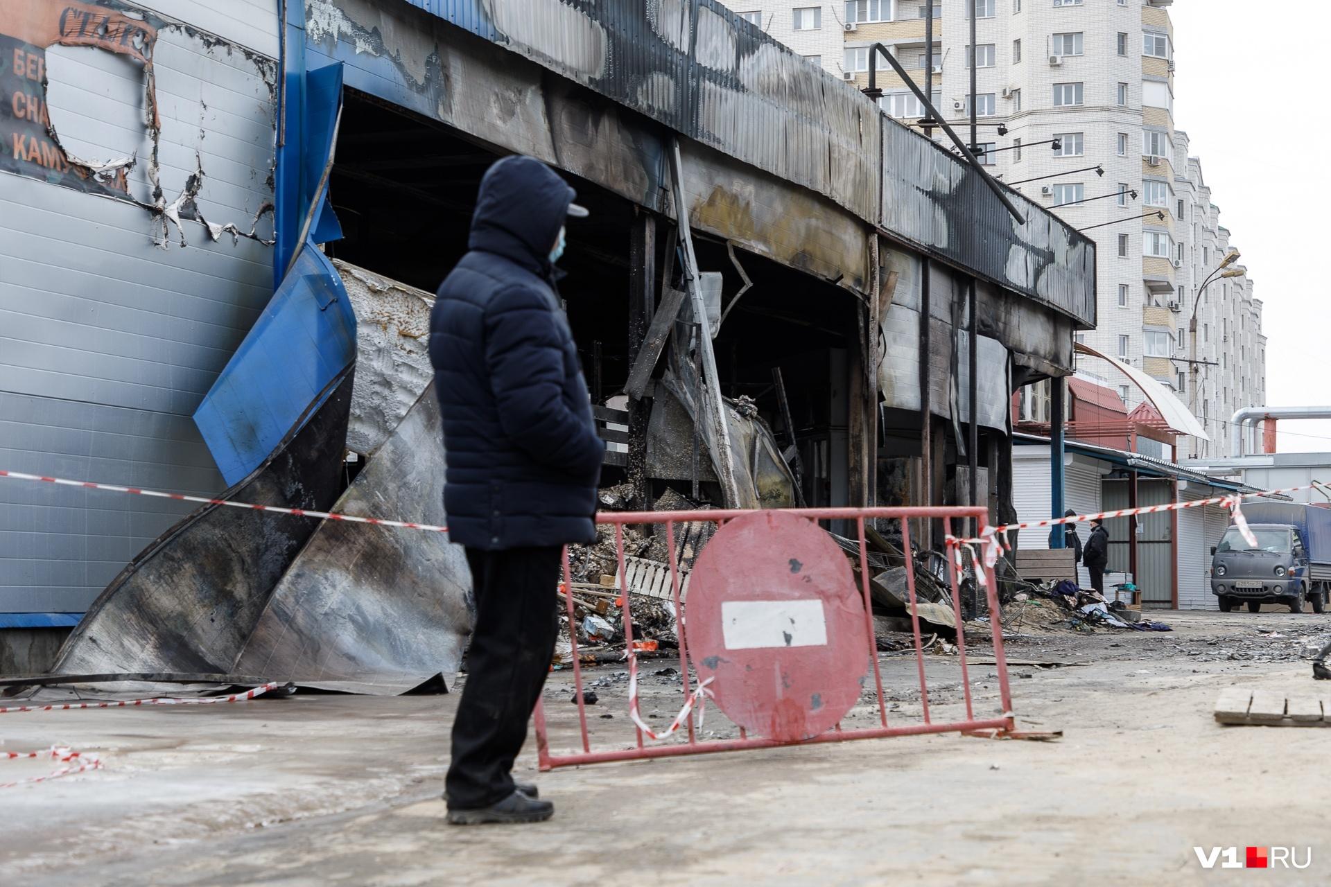 Торговцы подходят к сгоревшему павильону, где уничтожен товар на миллионы рублей