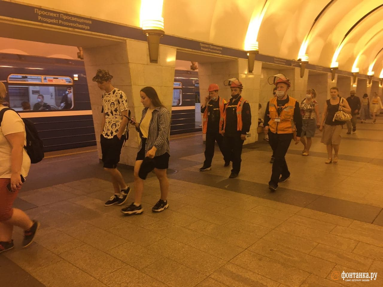 Сотрудники метро ходят по станции.