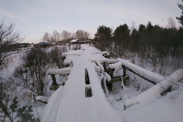 Сейчас добираться до цивилизации трем жителям деревни приходится с помощью такой конструкции. Этот мост построили еще в советские годы
