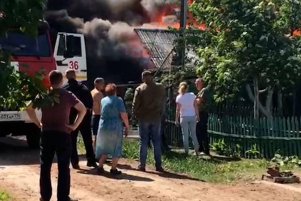 Дома на этой улице стоят вплотную друг к другу. Пожарные стараются не допустить, чтобы огонь перекинулся на соседние постройки