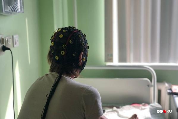 Пациентов с эпилепсией диагностируют с помощью специального оборудования. На женщине надет чепчик с электродами