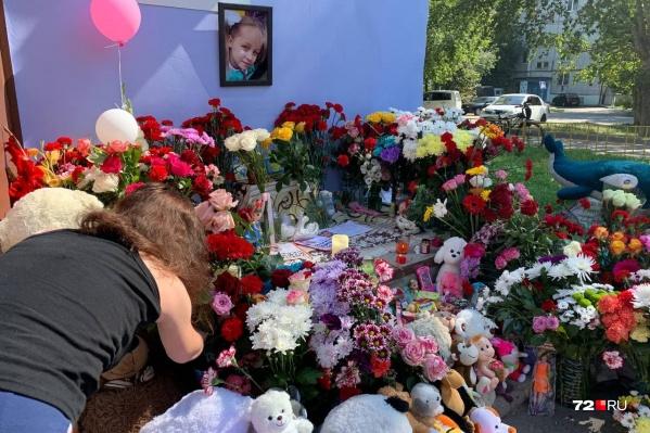Стихийный мемориал у дома Насти: красные гвоздики, шоколадки, записки с сожалениями о смерти девочки. И много разных игрушек, среди которых были и вещи убитого ребенка