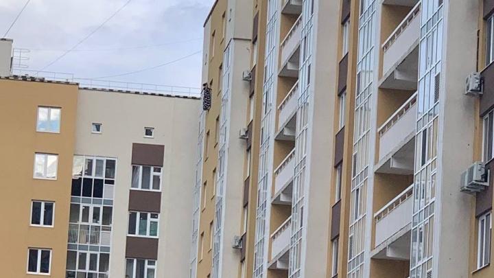 К многоэтажке на Зелинского в Тюмени съехались полицейские из-за девушки, повисшей с высоты