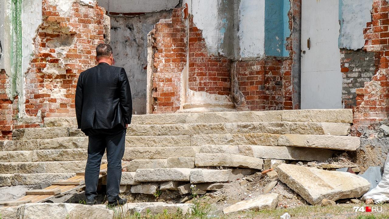Чиновник разглядывает разрушенный храм (здание восстанавливают)