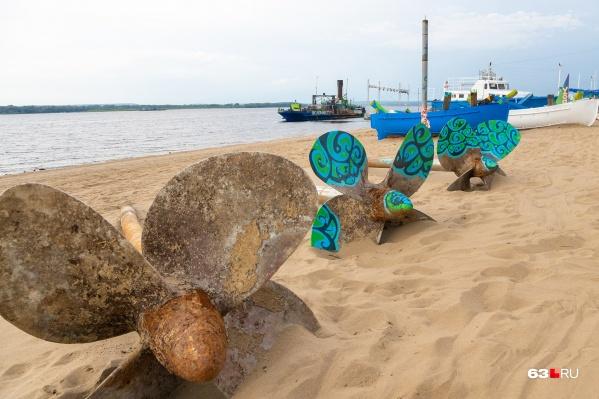 На песчаном пляже расположились составные части кораблей