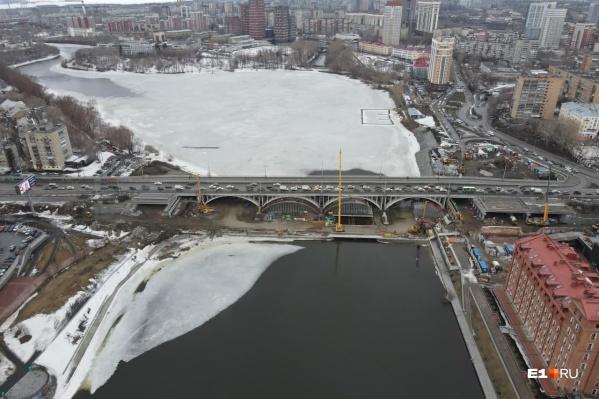 От левого берега Исети к середине пруда уже стоят пролеты будущего моста