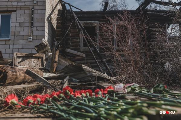 На месте трагедии у дома лежат цветы