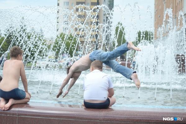 Те, кому не хватило места у водоема, спасаются от жары в фонтанах