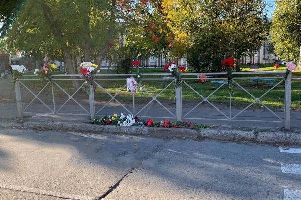 Люди приносят к месту гибели юноши цветы