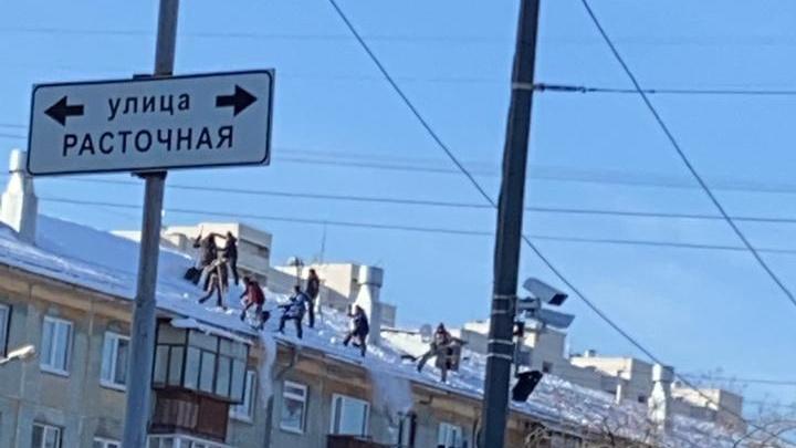 Смертельный трюк: очевидцы сняли, как восемь дворников без страховки чистят крышу пятиэтажки на Сортировке