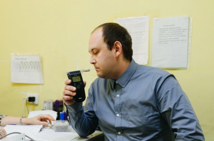 Медик проверяет температуру, давление и содержание алкоголя