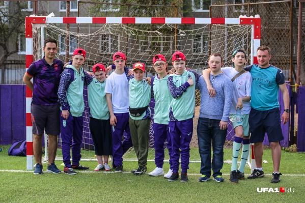 Игроки ФК «Уфа» Денис (крайний слева) и Василий (крайний справа) тренируют детей с синдромом Дауна