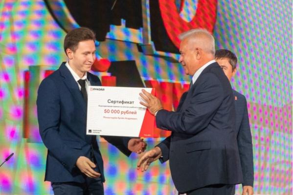 Студент Политеха Артём Монастырёв получает сертификат на премию от президента «ЛУКОЙЛа» Вагита Алекперова
