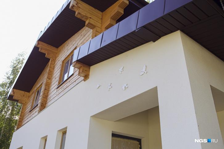 Над парадным входом в дом «летают» соловьи — дань названию коттеджного поселка