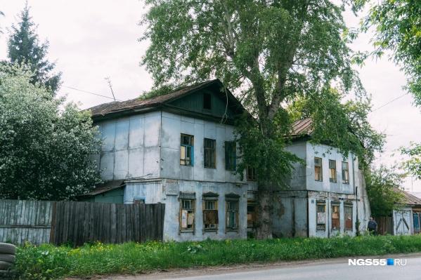 Разрушающийся дом прячется за цветущей зеленью окружающих его деревьев