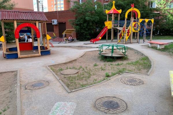 О том, что детская площадка стоит на сетях водоснабжения, можно понять по люкам колодцев
