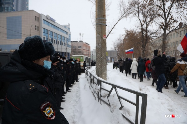 Полицейские плотной цепью стоят вдоль проезжей части. Участники акции идут по пешеходным тротуарам