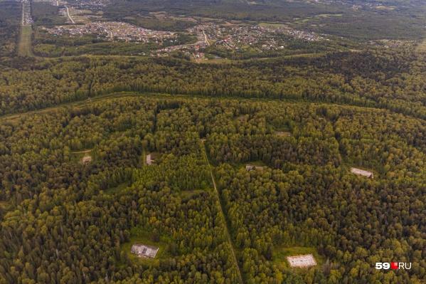 Территория бывшего полигона. Светлые прямоугольники на фото с высоты — разрушенные военные склады. На дальнем плане жилой поселок