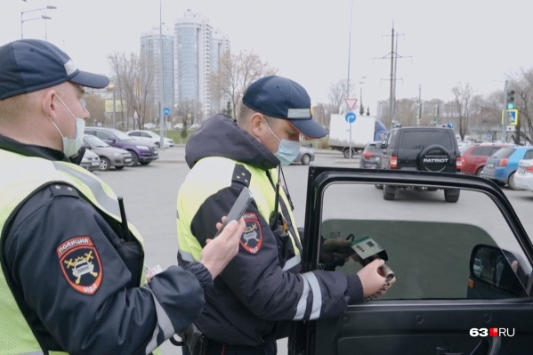 Дорожные полицейские проверяют светопропускную способность стекол специальным прибором