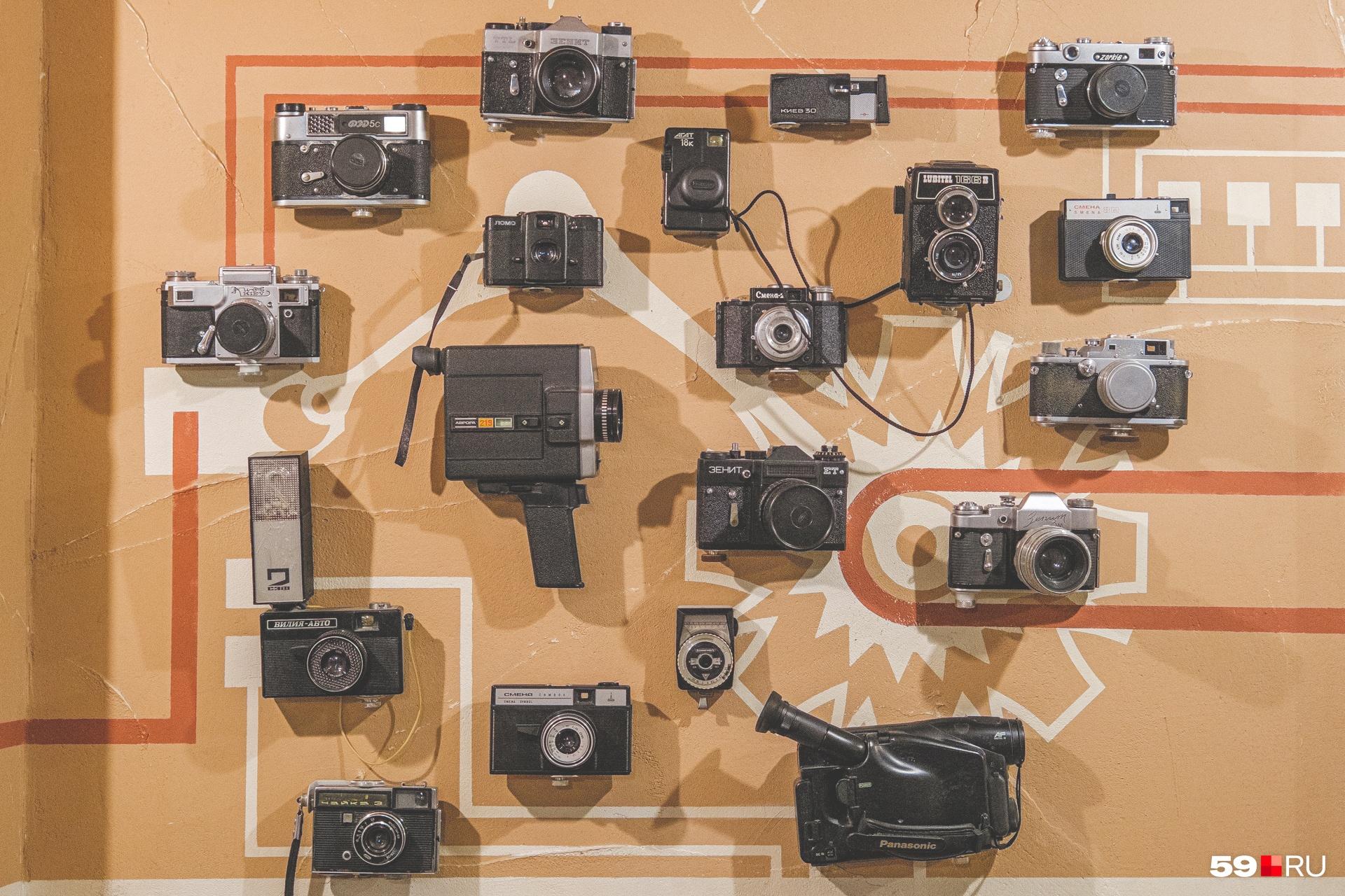 На этой стене сначала висел всего один старый фотоаппарат. Остальные подарили посетители: им понравилась идея так украсить помещение