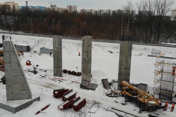 Рабочие продолжают строительство конструкций, чтобы провести дорогу над рельсами