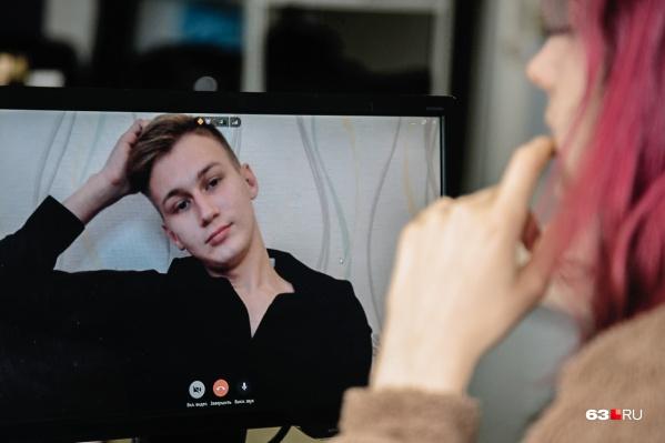 Молодой человек общается со своими клиентами по видеосвязи
