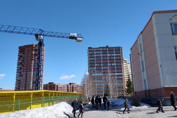 Строительный кран работает рядом со школой, но застройщик уверяет, чтогруз не может оказаться за пределами строительной площадки