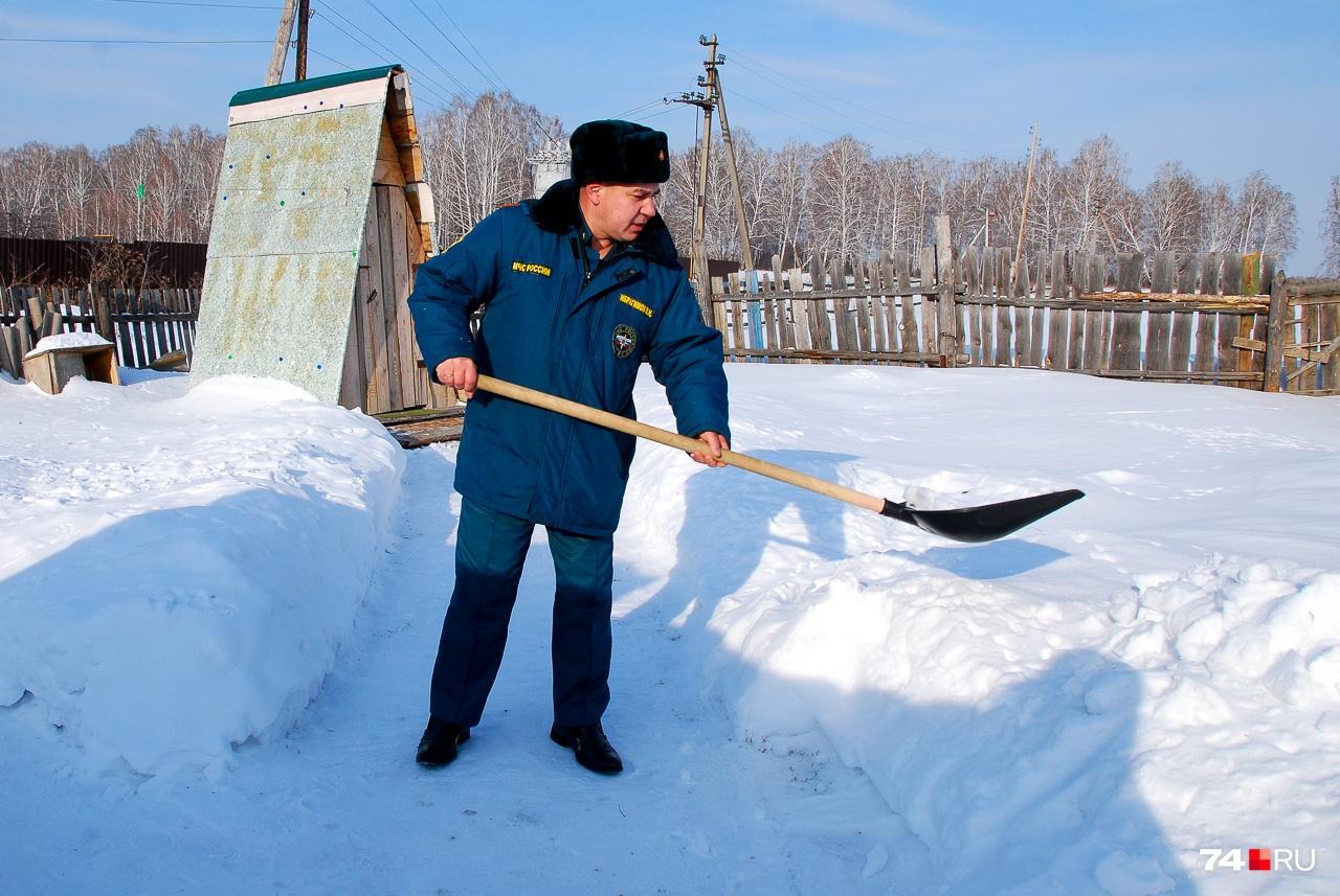 Виталий расчищает дорожку к уличному туалету