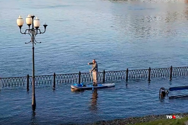 Мужчина плавает между затопленными лавочками и фонарями