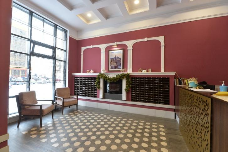 В холле второго дома стены цвета марсала отлично сочетаются с золотыми элементами декора стойки администратора и почтовыми ящиками из темного дерева