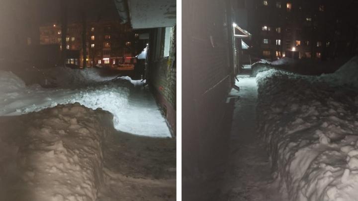 «Там снега по пояс»: во дворе на Блюхера почистили крыши домов и завалили снегом проезды и парковку