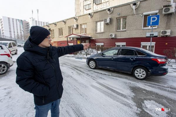 Андрей Косухин показывает место, где еще недавно был знак «Парковка для инвалидов»
