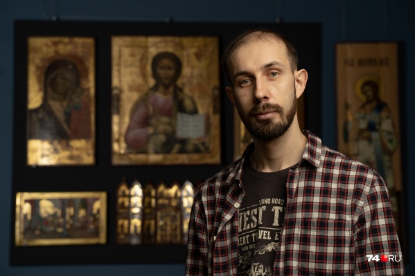 Виктор Чичиланов позирует на фоне отреставрированных им икон, они — часть постоянной экспозиции челябинского музея
