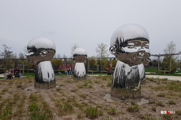 Четыре скульптуры стоят спиной друг к другу на клумбе