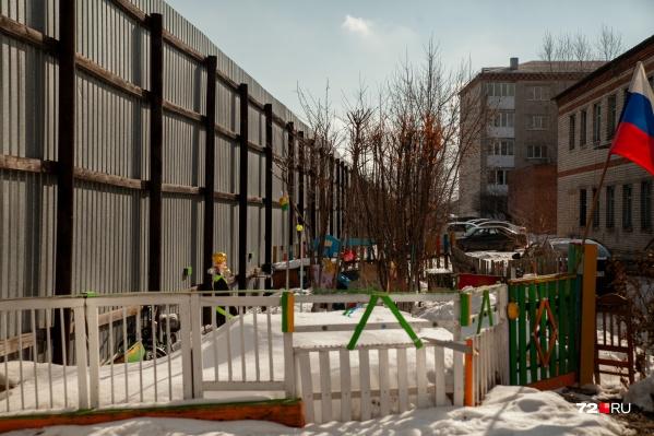 Жилые дома и колония разделены высоким забором