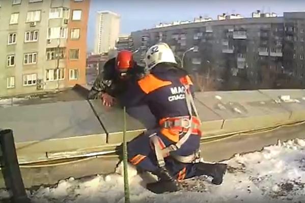 Спасатели обвязали мужчину веревкой, таким образом подстраховав его