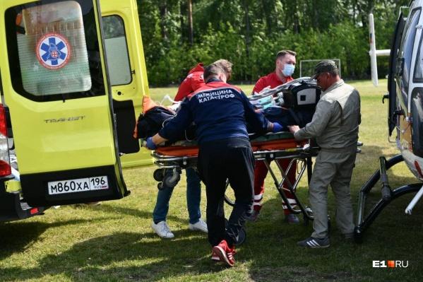 Первого пострадавшего переносят из вертолета в реанимобиль