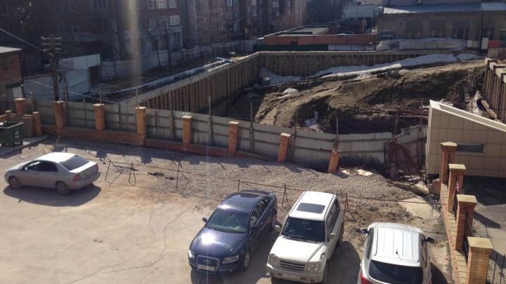 Кирпичный забор провалился в строительный котлован в центре Новосибирска