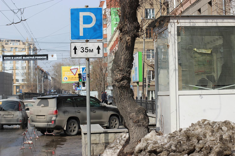 Муниципальную парковку перекрывают ограждениями, пуская сюда только клиентов салонов, а для охранника поставили будку