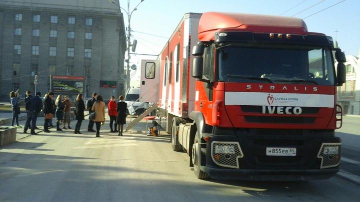 Новосибирцы выстроились в очередь к большой красной фуре посреди площади Ленина