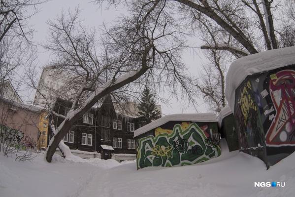 Необычный деревянный дом скрыт от пешеходов окружающими его многоэтажками и гаражами