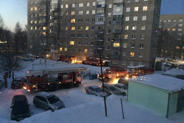 Около девятиэтажки стоят пять пожарных машин