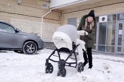 Молодая мама в ролике пробирается с коляской через заснеженный двор