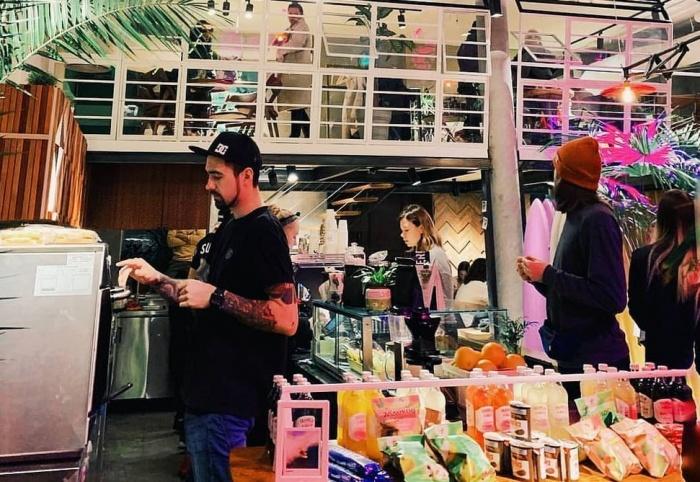 В кофейне, как в тропиках — растут пальмы и стоят доски для сёрфов