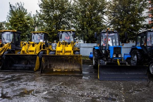 Трактор дорожных служб счищал грязь с асфальта металлическим ковшом