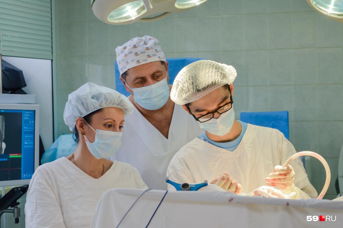 Заведующий отделением нейрохирургии наблюдает за ходом операции, которую проводят его сотрудники