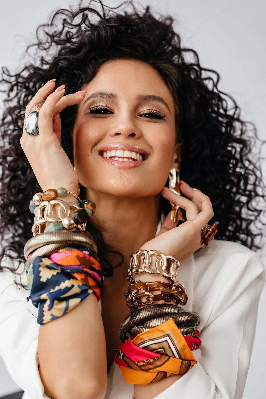 Акцентом в образе стали аксессуары — массивные браслеты, крупные кольца и яркие платки<br>