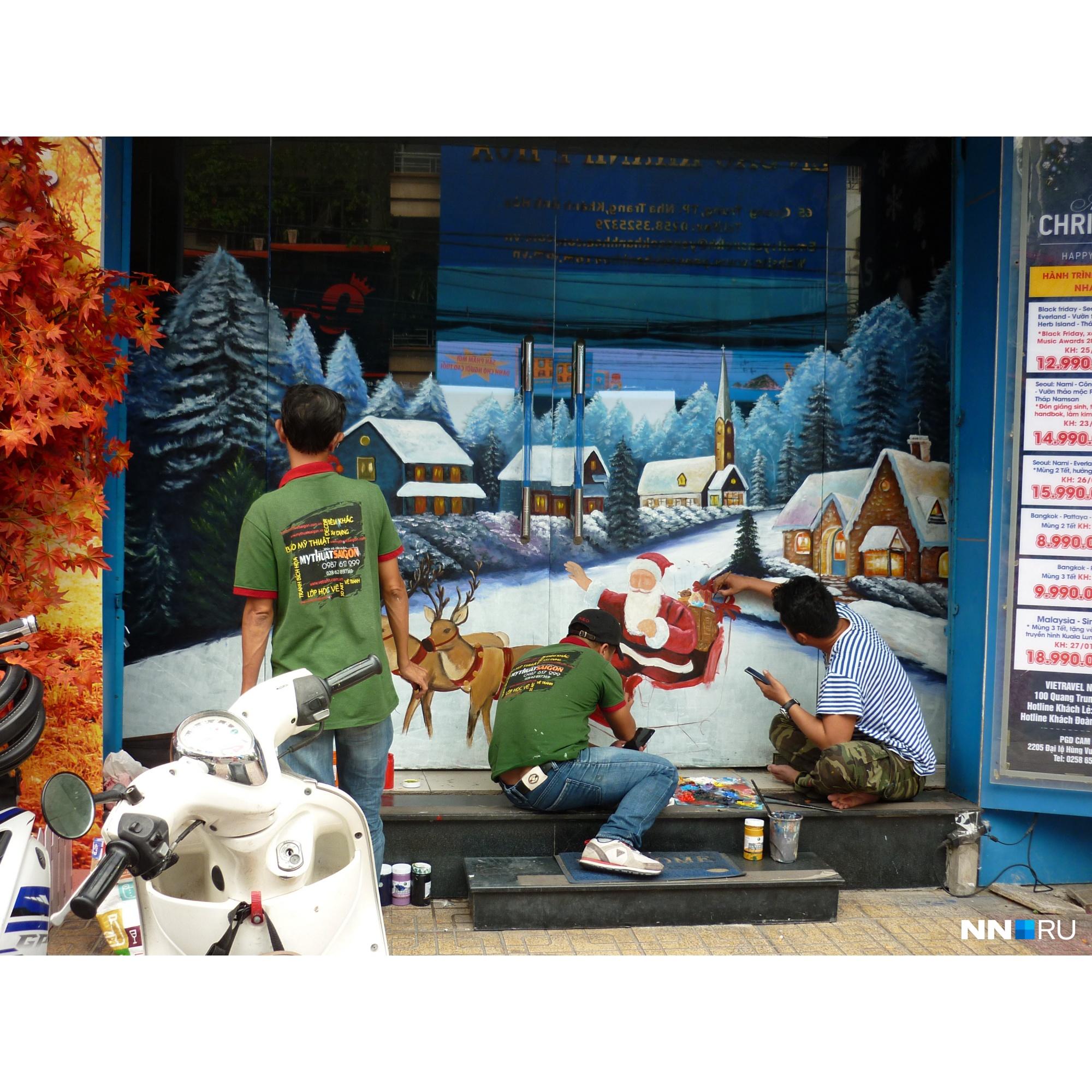 Художники наносят на двери магазина рождественское изображение<br>