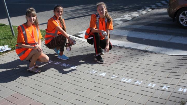«Сними наушники немедленно»: на тротуарах перед пешеходными переходами появились необычные надписи