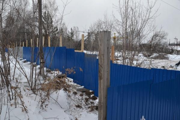 За ветками деревьев видно два новых дома, которые должны стать частью будущего микрорайона